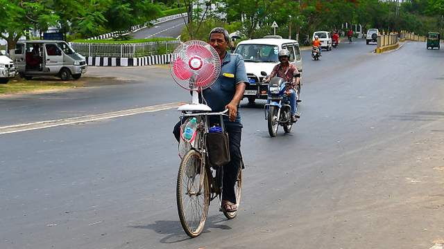 A city dwellers returns home after buying a stand fan to beat scorching heat. Image: Indigenousherald
