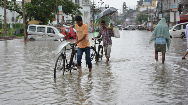 Commuters wade through a water logged street in Agartala in aftermath of incessant rains. Image: Indigenousherald